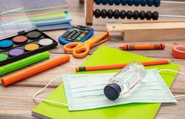 Children's school supplies with medical mask and hand sanitizer (stock image).